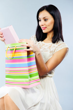 Beautiful brunette taking out present from shopping bag